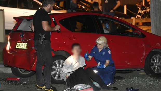 One of the teens is checked for injuries after his arrest. Picture: Gordon McComiskie