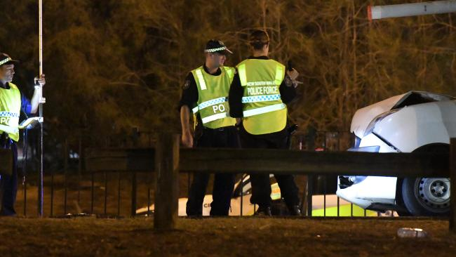 Police examine the scene where their colleagues were injured. Picture: Gordon McComiskie