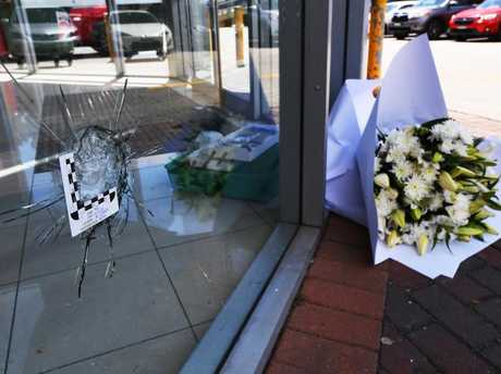 A bouquet of flowers by a bullet hole Fitness First in Rockdale after Hawi's fatal shooting. Picture: David Moir.
