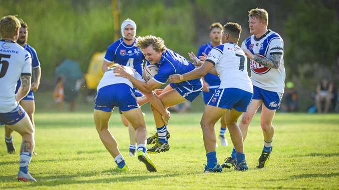 ALMOST THROUGH: Brisbane Valleys' Jon Collins bursts through the defence of Gladstone's Jai Parter and Michael Ruge on Saturday
