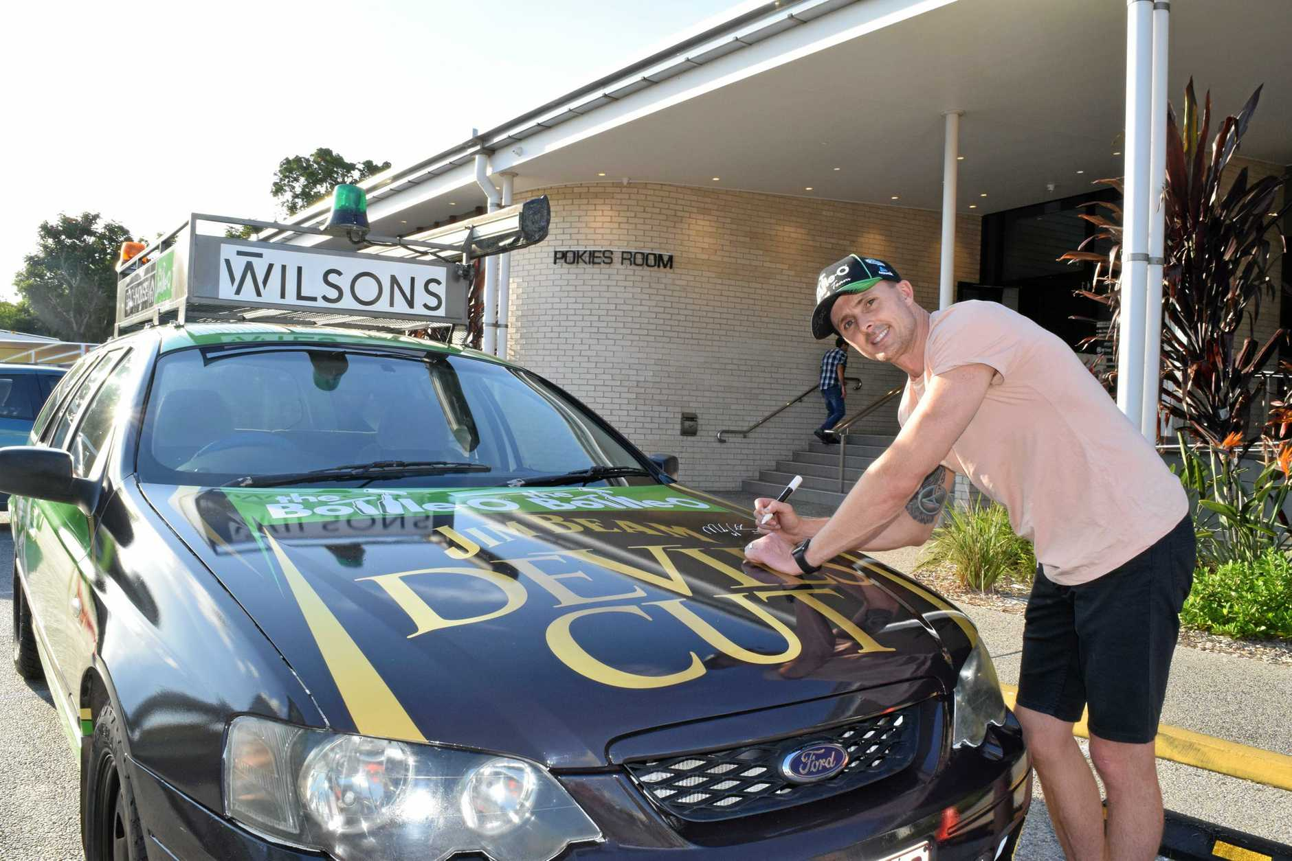 BLESSING OF THE VEHICLE: Supercars ace Mark Winterbottom signs the official 2018 Dunga Derby vehicle at the Beach House Hotel on Saturday.