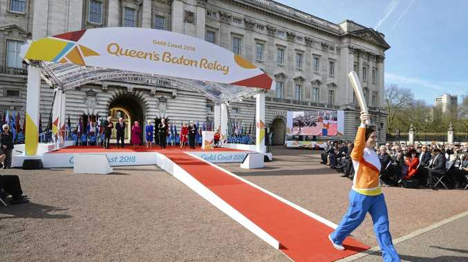 Retired cyclist Anna Mears from Australia, right, carries the Commonwealth Games relay baton that she received from  Britain's Queen Elizabeth II,  centre left,  at the launch of the relay at Buckingham Palace in London Monday March 13, 2017.  The XXI Commonwealth Games are  being held on the Gold Coast in Australia in 2018. (John Stillwell/Pool via AP)