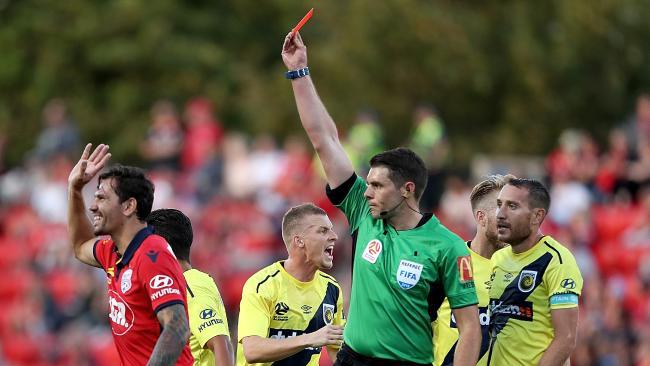 Referee Shaun Evans sends off Adelaide United defender Ersan Gulum.