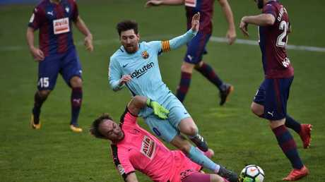 FC Barcelona's Lionel Messi is tackled by SD Eibar's goalkeeper Marco Dmitrovic