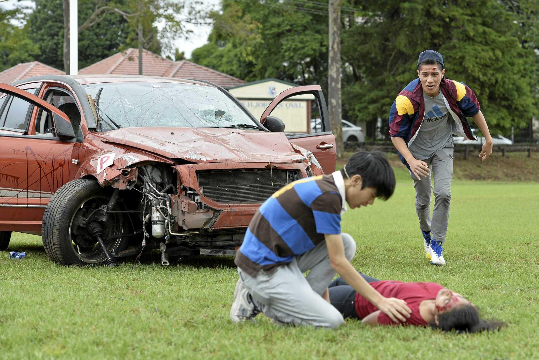 TACAPS students (from left) Joseph Goh, Jasmine Barui and Kalisi Fonua act out the fatal car crash scenario as part of road safety education program, RACQ Docudrama, Tuesday, February 20, 2018.