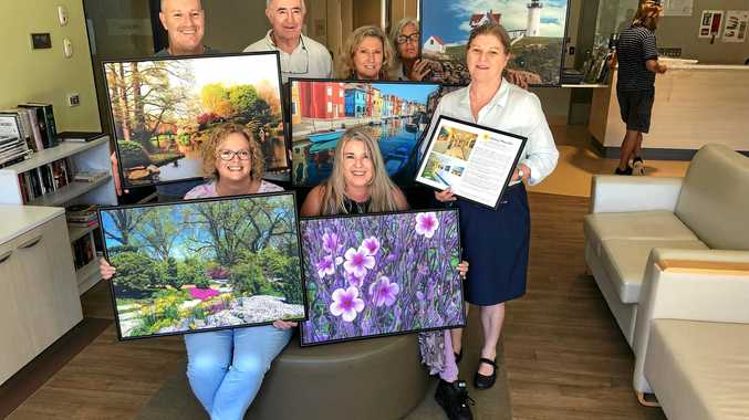WINDOWS: Jim Hourigan from Healing Photo Art (back row second from left) and Kathryn Blaich (bottom left) with Tuckeroo staff and 5 of 30 picture that will grace the facility's walls.