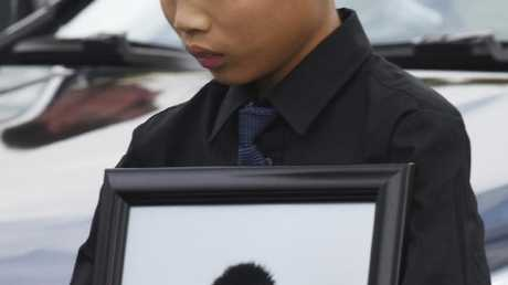 Alex Wang holds a picture of brother Peter after the funeral. Picture: Taimy Alvarez/South Florida Sun-Sentinel via AP