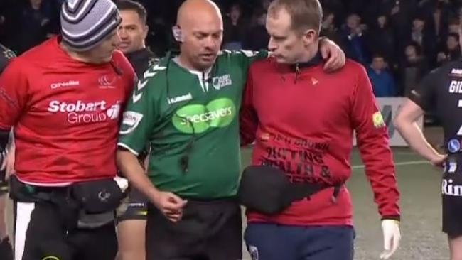 Referee Phil Bentham is attended to by trainers.