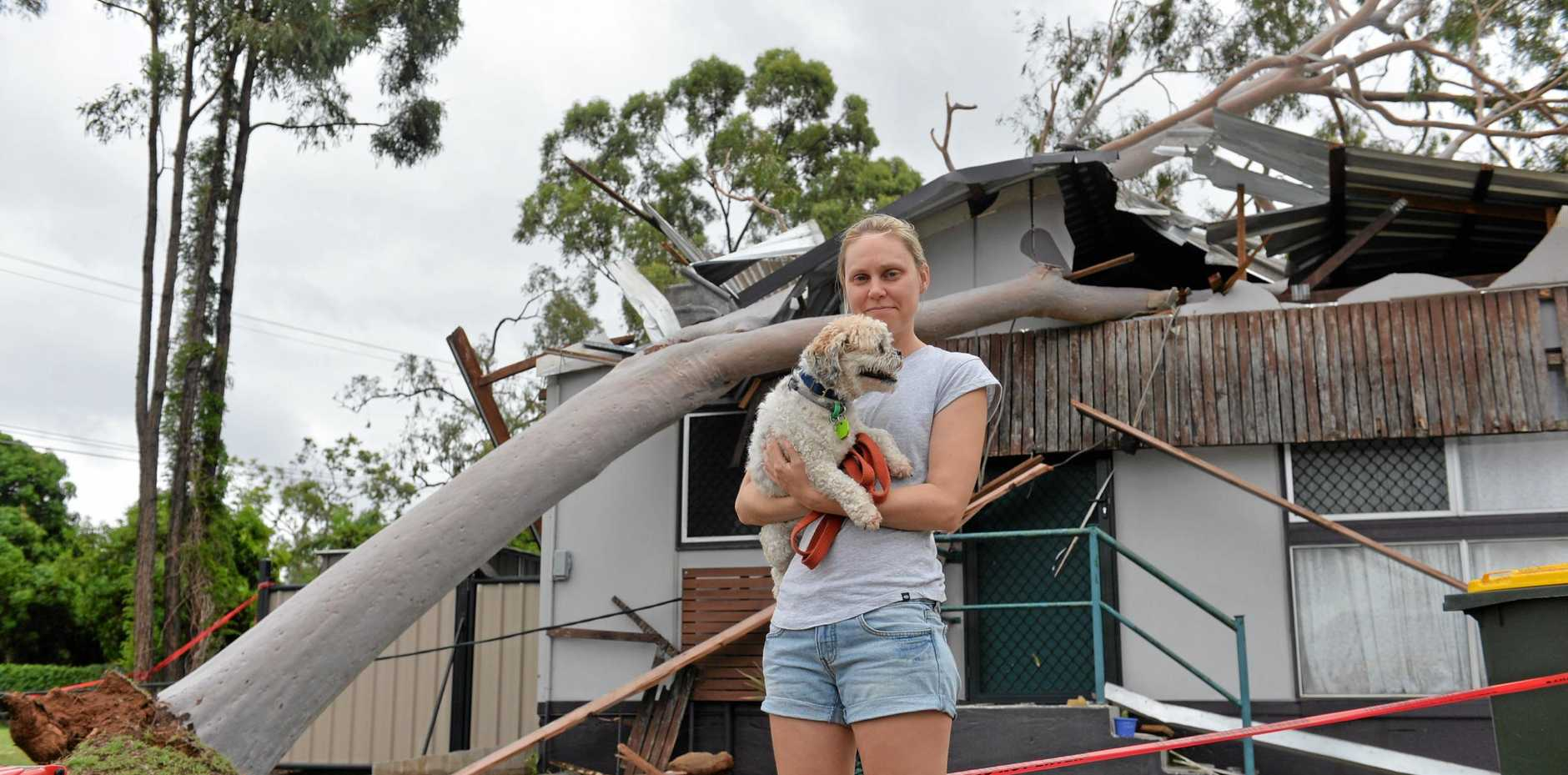 Kelly Young and her dog Ralph outside their Archer St home in Moranbah after cyclonic winds swept through the central Queensland town.