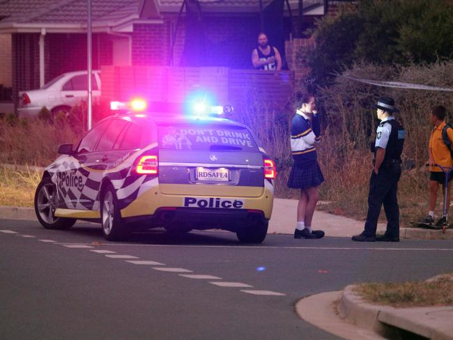 Police speak with a neighbour after a woman and two children were found deceased in the house on Peter Coppin Street, Bonner. Picture: Gary Ramage.