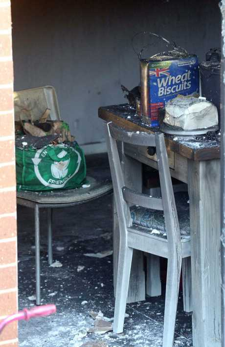 Breakfast cereal sits on a table and a shopping bag on a chair inside the charred Canberra home where three bodies were found on Monday. Picture Gary Ramage.