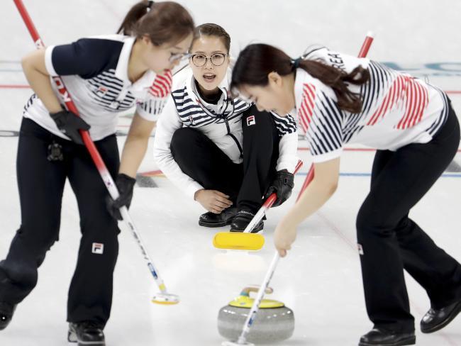 South Korea's Kim Seon-yeong, left, and Kim Yeong-mi, right, sweep the ice as tskip Kim Eun-jung, centre, looks on. (AP Photo/Natacha Pisarenko)