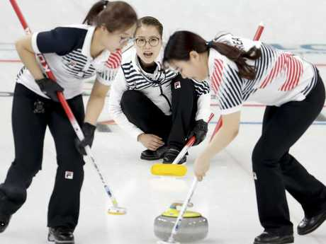 South Korea's Kim Seon-yeong, left, and Kim Yeong-mi, right, sweep the ice as tskip Kim Eun-jung, centre, looks on. (AP Photo/Natacha Pisarenko)