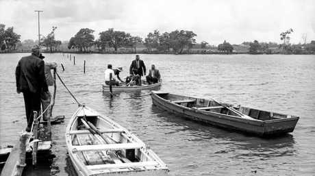 Then minister for lands Alan Fletcher and party crossing Eudlo Creek by boat during his visit to the Maroochy Shire in November 1963. During his visit, he and Maroochy Shire Council chairman David Low (pictured standing in boat) discussed proposals for the completion of the coastal highway.