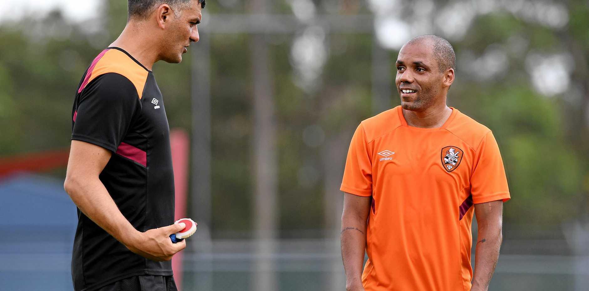 John Aloisi talks with Henrique at training.