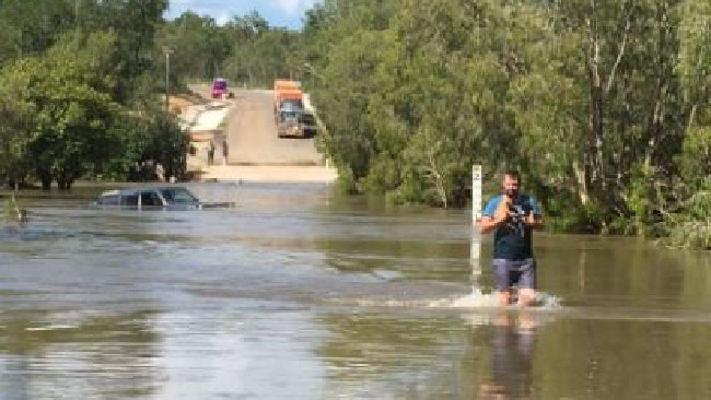 Coen police Senior Constable Ben Lloyd rescuing two five week old puppies from floodwaters at Archer River.