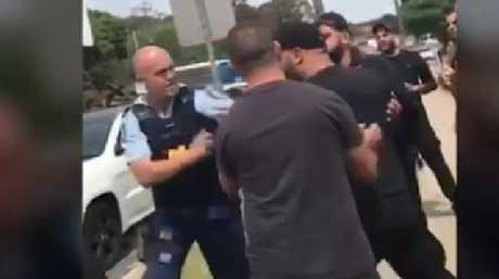 The police officer is forced to push one of the men away as he gets in his face. Picture: Supplied