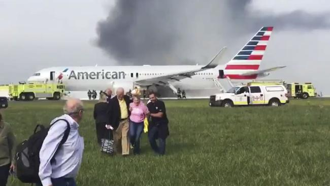 Passengers walk away from a burning American Airlines jet — with their luggage.