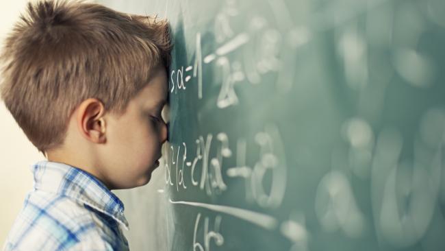 Little boy in math class overwhelmed by the math formula.