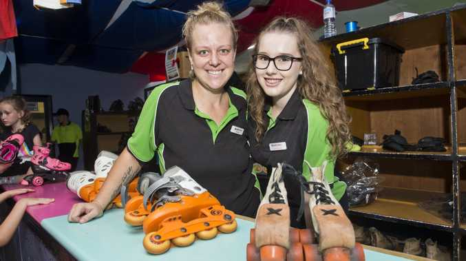 Skate City staffers Shauni Hopkins and Hannah Reichle hand out the roller skates on the venue's last day on Sunday.