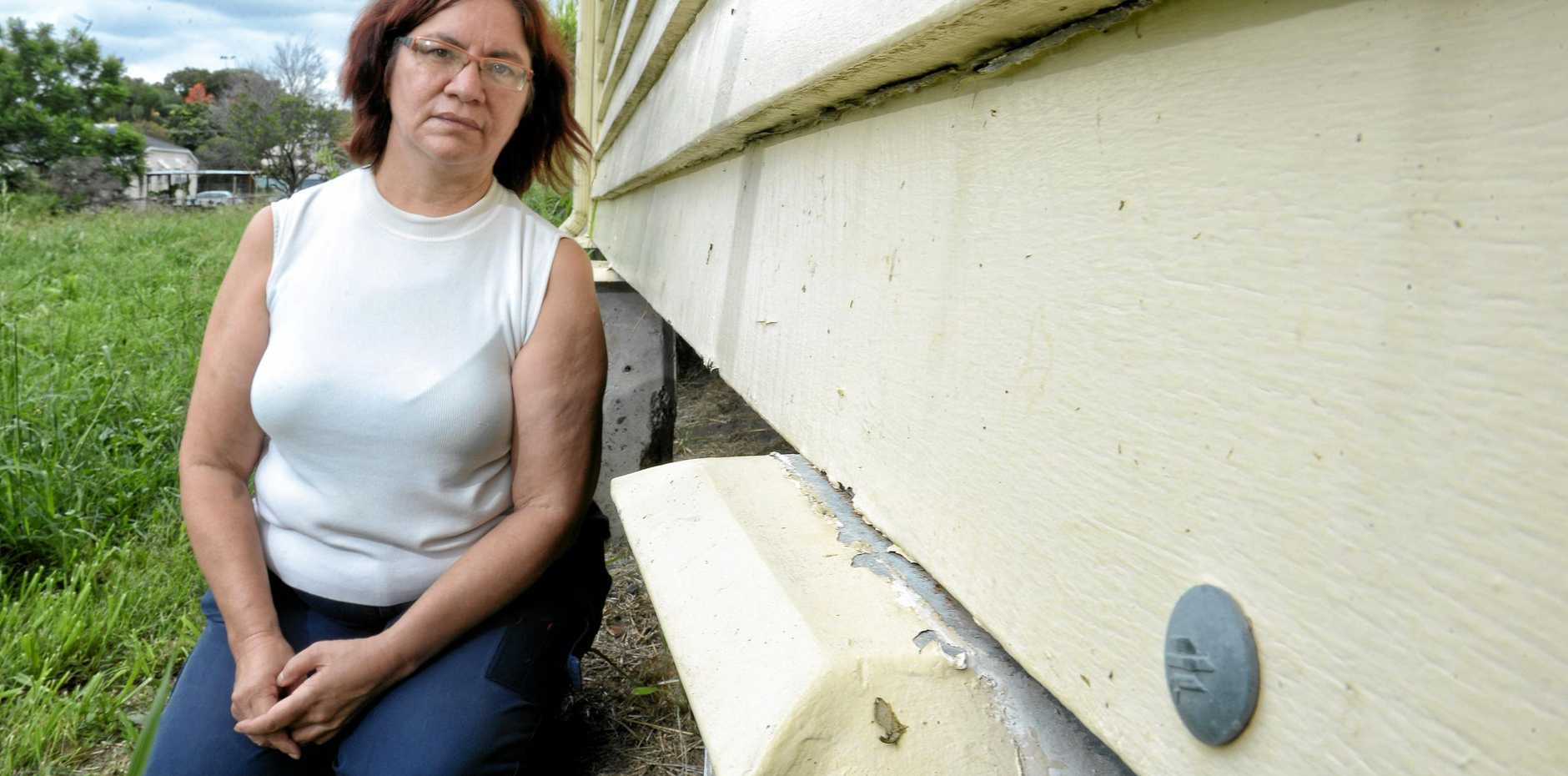 INSURANCE CLAIM: Jessie Harlow inspects the damage to her North Ipswich home she believes was caused by high winds in a storm in October last year.