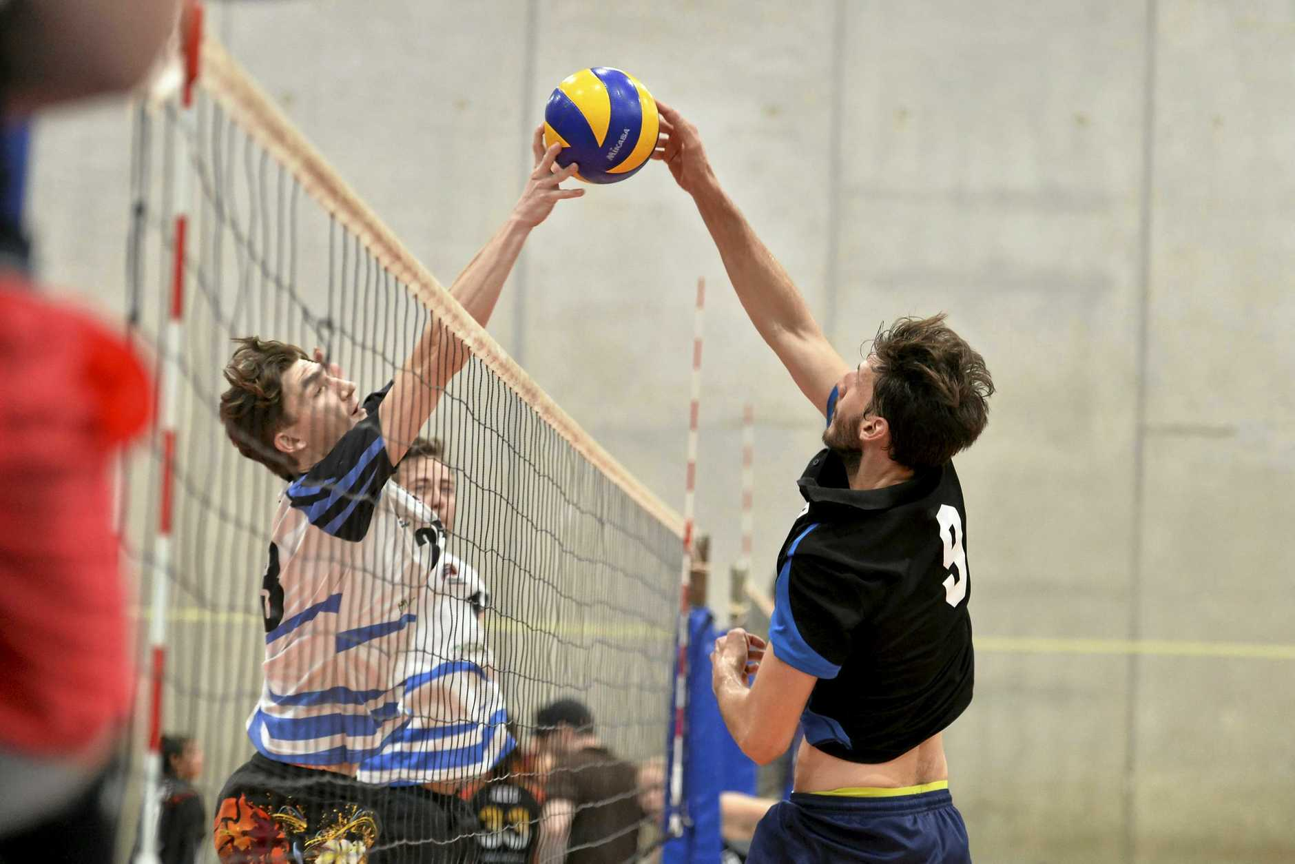 NET BATTLE: Brisbane Volleyball Club'S Connor Rudder (left) and Remember the Titans player Marco Calderini do battle at the net in the final of the Clash of the Titans volleyball tournament at Harristown State High School gym. Brisbane won the final 2-1.