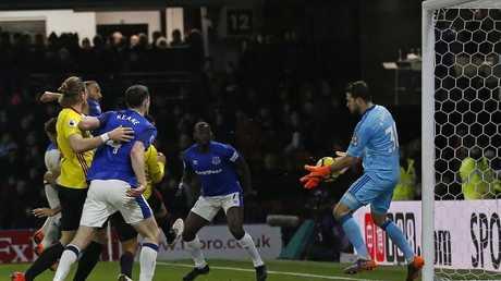 Watford's Greek goalkeeper Orestis Karnezis (R) saves from a close-range header from Everton's Turkish striker Cenk Tosun