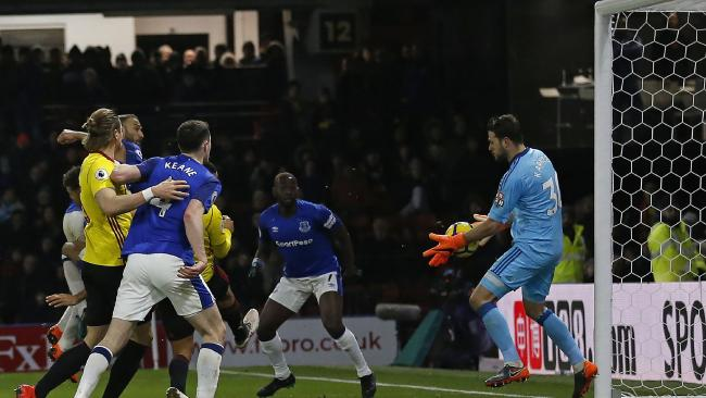 Watford's Greek goalkeeper Orestis Karnezis (R) saves from a close-range header from Everton's Turkish striker Cenk Tosun