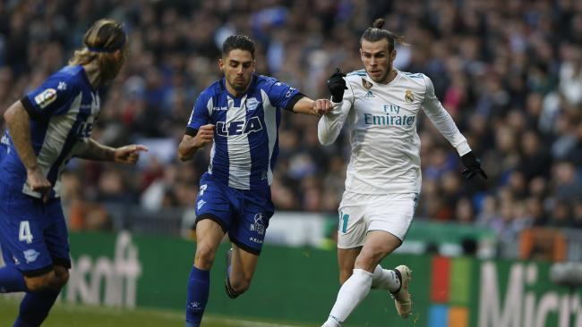 Real Madrid's Gareth Bale, right, tussles for the ball with Alaves' Ruben Sobrino