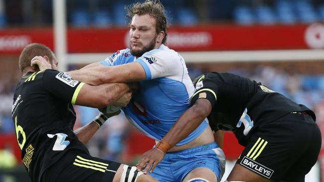 Bulls lock RG Snyman is tackled by Hurricanes captain Brad Shields and Sam Lousi.