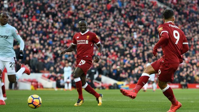 Liverpool's Brazilian midfielder Roberto Firmino (R) scores a cheeky no look goal