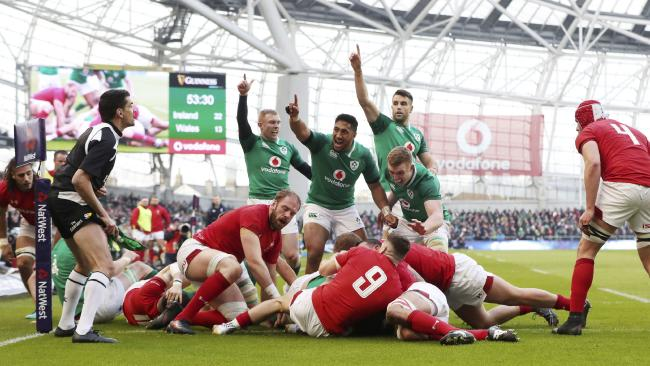 Ireland players claim a try by Cian Healy, obscured under Wales players.