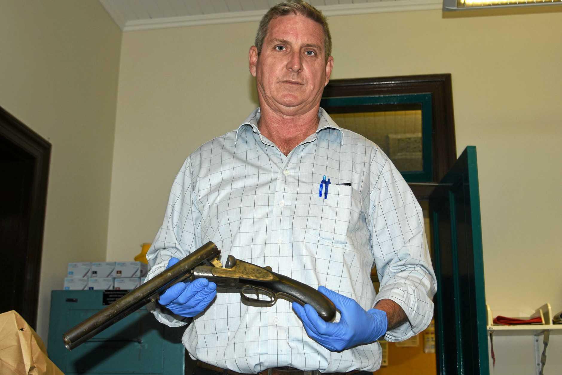 FOUND: Detective Sergeant Darren Tamblyn holds the shotgun.