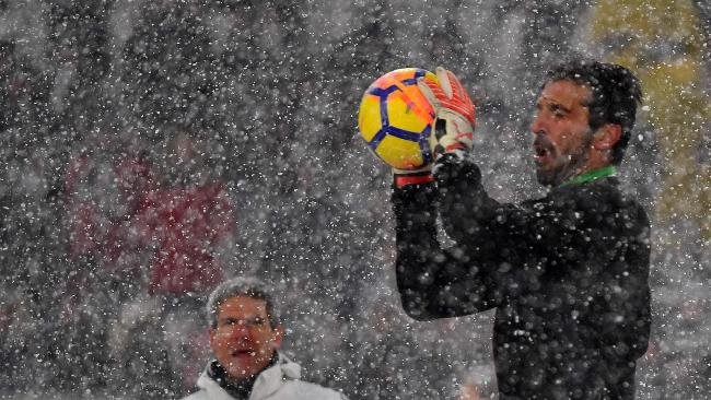 Juventus's Italian goalkeeper Gianluigi Buffon (R) catches the ball under heavy snowfall