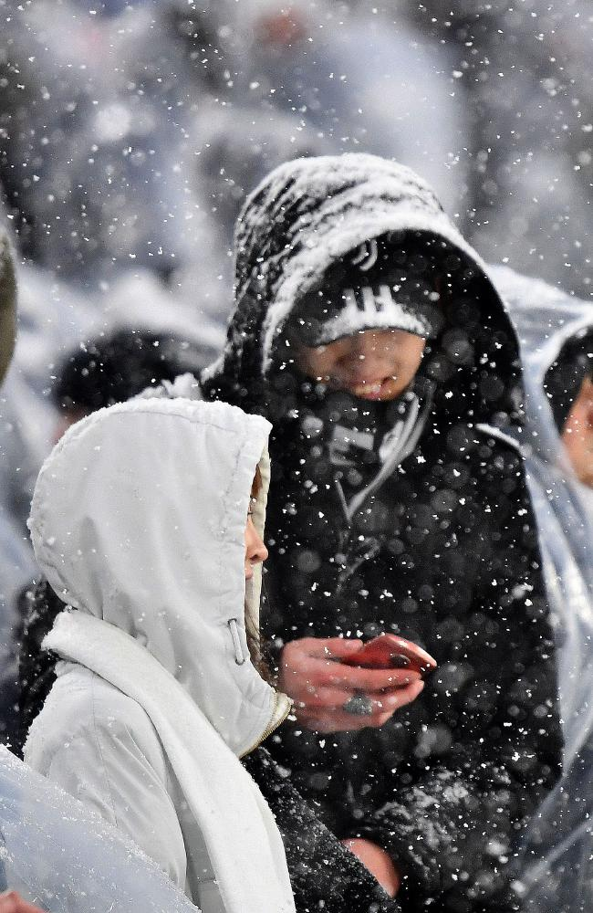 Supporters look on under heavy snowfall