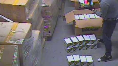 CCTV shows one of the accused loading the highlighters into packets. Picture: AFP