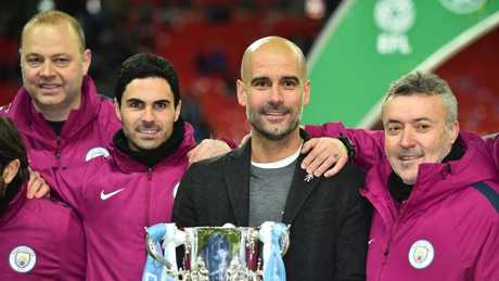Manchester City's Spanish manager Pep Guardiola holds the trophy