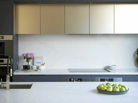 A contemporary example of champagne metallic used to colour-block against charred grey cabinetry.