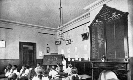 View from the back of the room looking towards the teacher, of a classroom in the Girls' Grammar School at Maryborough around 1890.