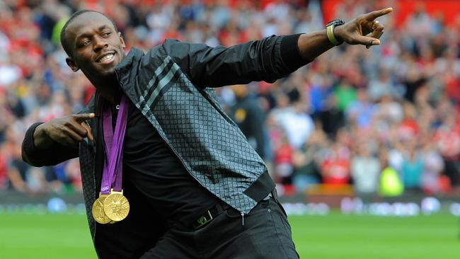 Usain Bolt on the Old Trafford pitch in 2012 with his medals from the 2012 London Olympics.