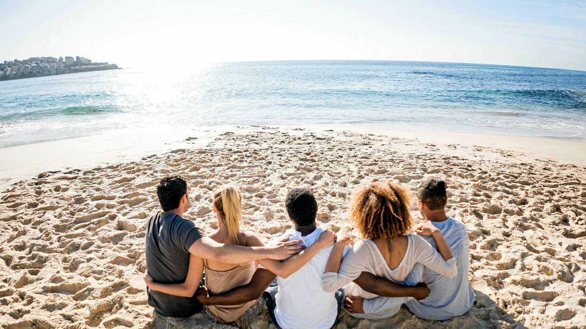 Happy group of friends relaxing at the beach and looking at the sea while sitting in the sand