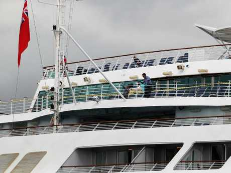 Cleaners clean the railings of the Sun Princess after it docked in Brisbane following an outbreak of norovirus in February 2017. Picture: Claudia Baxter