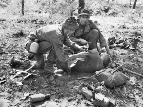 A medic and a sergeant apply first aid to Private Jim Richmond twelve hours after the Long Tan battle. He was shot twice through the chest and lay all night, face down, at his section post.