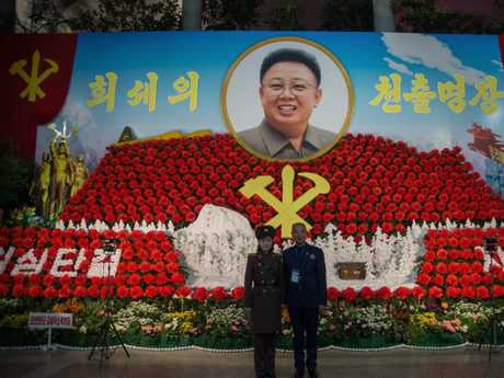 North Koreans in front of a portrait of Kim Jong-il. The late leader used to visit the west on fraudulent Brazilian passports. Picture: AFP/Kim Won-Jin