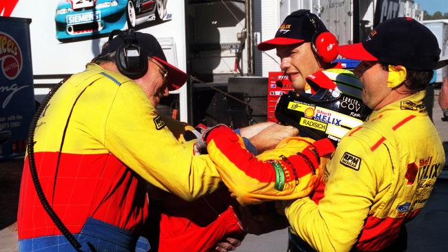 Paul Radisich being carried from his car by pit crew members after suffering dehydration in the heat in 1999.