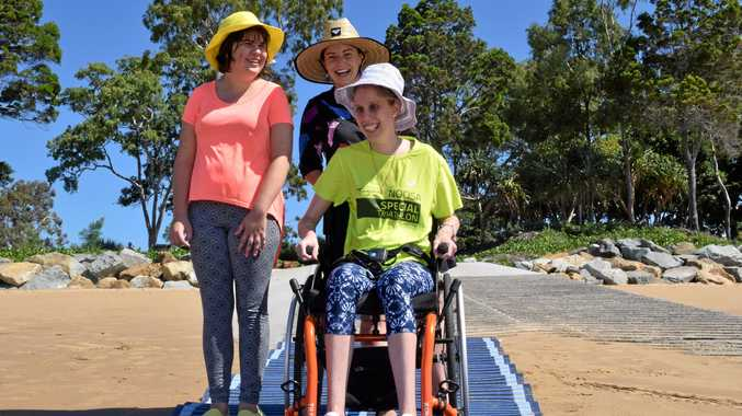 ROLLING ON THE BEACH: Community Lifestyles Agency Business Manager Jess Lane (centre) with Bella Kupke (left) and Shelbie Adam (right) trialling the roll-out of the beach access mat.