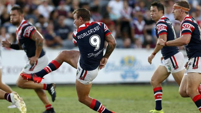 Jake Friend of the Roosters puts in a kick down field.