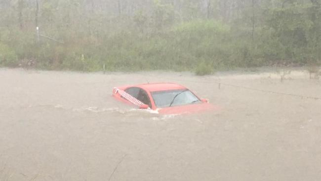 A red Holden Commodore is inundated with water after the driver crashed late last night.