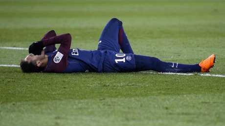Paris Saint-Germain's Brazilian forward Neymar Jr reacts lying on the pitch