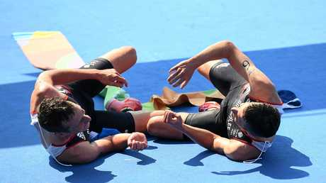 Alistair Brownlee (left) and his brother Jonathan Brownlee celebrate on the ground past the finish line after winning the men's triathlon at Fort Copacabana during the Rio 2016 Olympic Games.